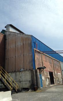 Au bas d'ancienne usine d'électrolyse, des ouvertures servent à l'apport d'air (p. ex. l'ouverture à la droite de la porte bleue, condamnée par un panneau de bois). Au faîte du toit, une cheminée sert à l'évacuation de l'air