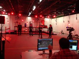 Aperçu d'une séance au studio capture de mouvements d'Ubisoft Montréal. À l'avant-plan, un moniteur permet à un employé d'Ubisoft de visualiser en temps réel la transposition des mouvements sur des personnages de jeu vidéo.